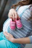 有桃红色赃物的愉快的未来母亲在手中 图库摄影