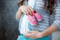 有桃红色赃物的愉快的未来母亲在手中 免版税图库摄影