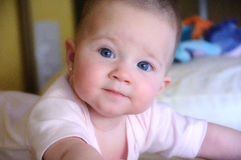 有桃红色身体的女性婴孩在床上 免版税库存照片