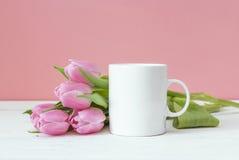 有桃红色郁金香的加奶咖啡杯子在桃红色背景 空间fo 免版税库存图片