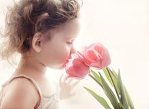 有桃红色郁金香的甜小女孩反对早晨阳光。 免版税图库摄影