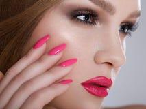 有桃红色钉子和豪华构成的美丽的妇女。红色性感的嘴唇和长的睫毛 免版税库存照片