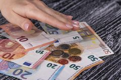 有桃红色钉子的妇女的手包括堆欧元钞票和硬币在一张黑老桌上 免版税图库摄影