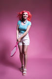 有桃红色头发的女孩打在桃红色背景的网球 库存照片