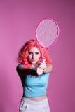 有桃红色头发的女孩打在桃红色背景的网球 免版税库存图片