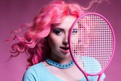 有桃红色头发的女孩打在桃红色背景的网球 图库摄影