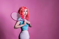 有桃红色头发的女孩打在桃红色背景的网球 免版税库存照片