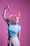 有桃红色头发的女孩打在桃红色背景的网球 免版税图库摄影