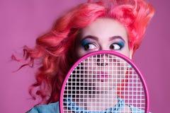 有桃红色头发的女孩打在桃红色背景的网球 库存图片