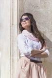 有桃红色围巾的年轻美丽的妇女对石墙 免版税库存图片