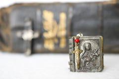 有案件的古色古香的念珠耶稣受难象与圣经在背景中 图库摄影