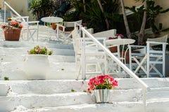 有桌和椅子的白色希腊台阶 典型希腊的街道 免版税库存照片