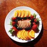 有桔子和苹果片断的板材  草莓和桑树 库存照片