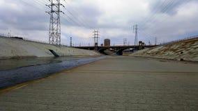 有桥梁和黑暗的天空的洛杉矶河在背景中 库存图片