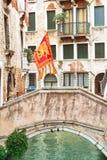 有桥梁的平静的运河和威尼斯式旗子在威尼斯 免版税图库摄影