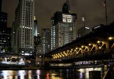 有桥梁的河在晚上照亮的摩天大楼 库存照片