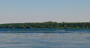 有桨的一个人在一条河的一条独木舟皮船小船航行在一个明亮的夏日反对岩石和海岛背景  免版税库存照片