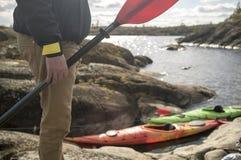 有桨的人在湖的岩石岸站立,反对 免版税库存图片