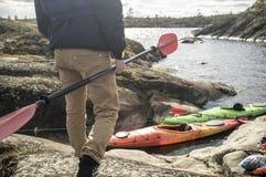 有桨的人在湖的岩石岸站立,反对 库存照片
