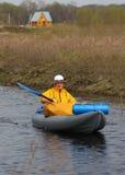 有桨的女孩一艘皮船和一个房子在背景中 库存图片