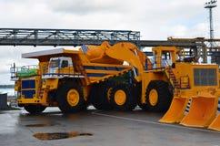有桶的一种挖掘机导致装载的沙子的模仿入一个大矿用汽车 免版税库存图片