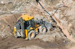 有桶的拖拉机挖掘机通过设置泥的土地乘坐赛跑,从高度的看法 库存图片