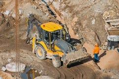有桶的拖拉机挖掘机通过设置泥的土地乘坐赛跑,从高度的看法 图库摄影