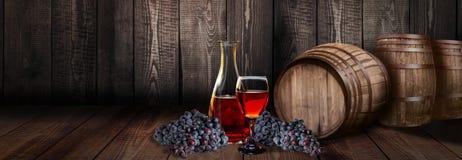 有桶的红葡萄酒玻璃瓶在葡萄园木头 库存照片