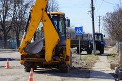 有桶的黄色挖掘机在被修理的柏油路站立 库存图片