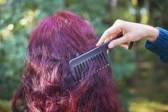 有梳妇女的红色头发的黑梳子的女孩的手 免版税库存图片