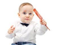有梳子的时髦的男孩在她的手上 免版税图库摄影