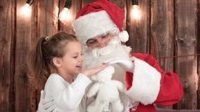 有检查圣诞老人` s胡子的玩具熊的小女孩 免版税库存照片
