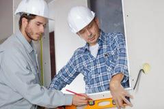 有检查的同事的年轻建筑工人平实 免版税库存照片