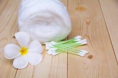 有棉花卷和白花的白色棉花芽在木t 免版税库存照片