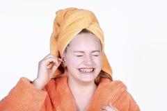 有棉花棒的笑的女孩清洁耳朵 画象少年在头的毛巾 免版税库存图片