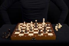有棋子的木棋盘在a前面的桌上 免版税库存图片