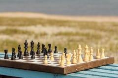有棋子的棋盘在与河embankm的长木凳 免版税库存照片