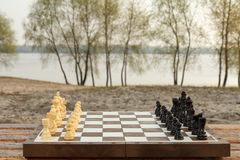 有棋子的棋盘在河堤防 一盘象棋 库存图片