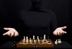 有棋形象的木棋盘和女孩的手 免版税图库摄影
