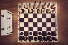 有棋的棋枰和时钟,顶视图,下棋比赛的起点 第一个移动 免版税库存图片