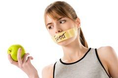 有棍子磁带的少妇有触击的通过词食物在手中看苹果的覆盖物嘴 库存图片