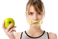 有棍子磁带的少妇有触击的通过词食物拿着苹果的覆盖物嘴 免版税库存图片