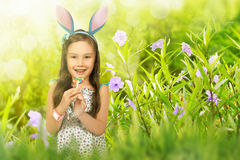 有棒棒糖佩带的兔宝宝耳朵的逗人喜爱的亚裔小孩女孩 库存图片