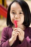 有棒棒糖的亚裔女孩 库存照片