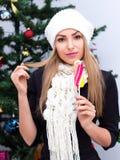 有棒棒糖的女孩在她的站立在圣诞树旁边的手上 库存照片