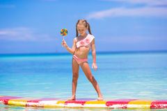 有棒棒糖的小女孩获得在冲浪板的乐趣  免版税库存照片