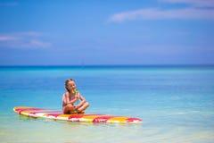 有棒棒糖的小女孩获得在冲浪板的乐趣  免版税图库摄影