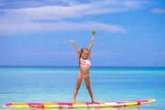 有棒棒糖的小女孩获得在冲浪板的乐趣  免版税库存图片