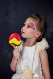 有棒棒糖的微笑的美丽的小女孩在白色有被绘的面孔的礼服红色嘴唇在黑暗的背景 儿童爱糖果 免版税库存照片