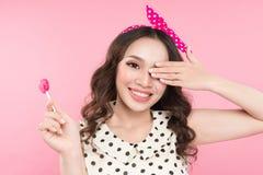 有棒棒糖的微笑的逗人喜爱的女孩,用手盖她的眼睛在p 免版税库存照片